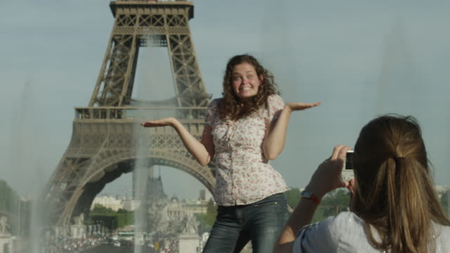 MS TU Young women taking photos in front of Eiffel Tower / Paris, France