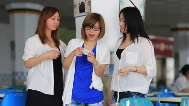 Young women using a degital tablet at a cafeteria