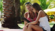 MS Young women using digital tablet outdoors / South Beach, Miami, Florida, USA