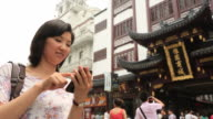 Young women using smartphone in Yuyuan Tourist Mart