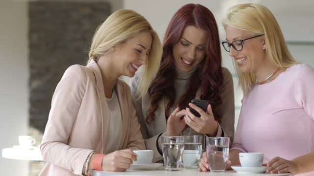 Young women using smartphone laughing in coffee shop.