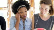 Young women using smartphones  sharing headphones and laughing