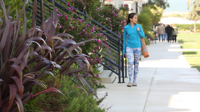 A young women walking outdoors with a yoga mat in a urban setting.