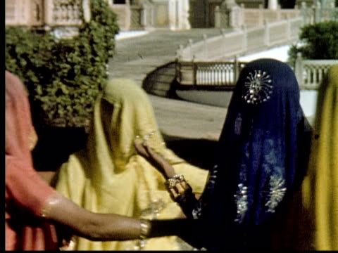 1960 MONTAGE Young women wearing saris and veils dance in circle in front of large white palace / India