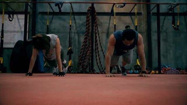 Young Women sporten in de fitnessruimte met personal Trainer