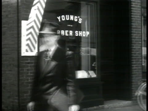 MS 'Young's Barber Shop' bicyclist pedestrian FG INT Barber applying shaving cream on man in chair others waiting BG Haircut New Hampshire