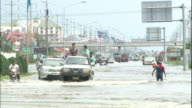 Youths play in a flooded Ayutthaya street as vehicles move past