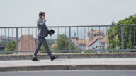 Yuppie talking on phone while walking across the bridge