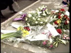 PC Yvonne Fletcher memorial TS Policewoman lays wreath on pavement by stoneTS Bouquets laid on pavementBV Woman lays wreath and kisses...