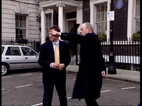 New information ITN ENGLAND London EXT Brady chatting to Richard Taylor as Taylor pointing to former Libyan Embassy building Memorial stone for...