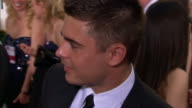 Zac Efron talking to reporter on the red carpet at the Beverly Hilton Hotel TU TD Golden Globe Awards sign
