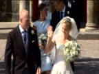 Zara Phillips and Mike Tindall walking out the wedding venue and waving