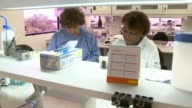 University of Pernambuco INT Professor Laura Rodrigues talkign with fellow scientist as working in laboratory/