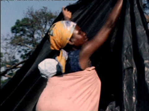 Zimbabwean war refugee sets up makeshift tent made for polythene to shelter her five children 1970s