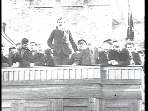 Zinovyev or Kamenev making speech/Funeral coffin carried through crowd on Red Square/Bolshevik leaders wave happily from Lenin's tomb w/ huge...