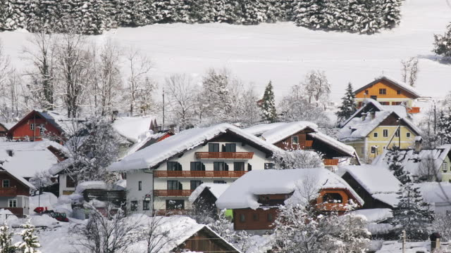 Zoom back from snowcovered roofs of Untersee village across frozen surface of Hallstattersee / Austria