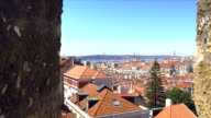Zoom from lisbon castello over the city rooftops towards cristobel and 25 de abril bridge.