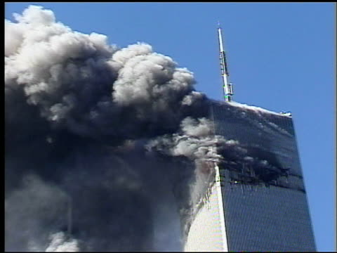 Zoom in and out as WTC Tower 1 burns / filmed from near Canal Street / CU view of transmitter on top of WTC Tower with billowing smoke in foreground...