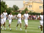 Zoom in and pan right as England striker Michael Owen jogs with rest of World Cup squad during training session in front of watching fans Portugal 17...