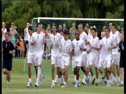 Zoom in as England's World Cup squad jog around training pitch during warmup session in front of watching spectators Portugal 17 May 06