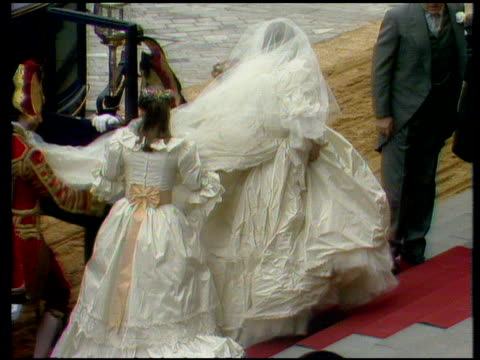 Zoom in as Lady Diana emerges from carriage attended to by bridesmaids walks up red carpeted steps with train behind her Royal Wedding of Prince...