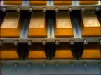 zoom in close up rows of 24K gold ingots sitting on metal trays / bottom tray moves out