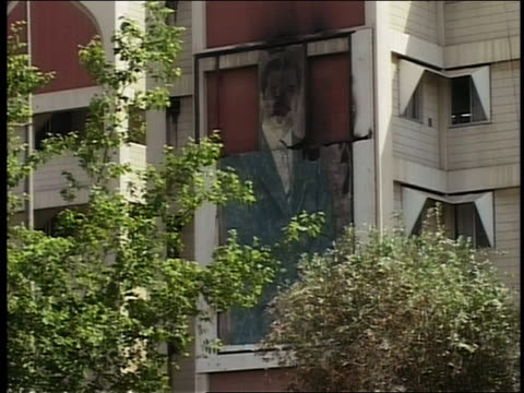 2003 zoom in damaged mural of Saddam Hussein on building / Baghdad Iraq