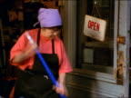 zoom in middle-aged Asian woman with bandanna on head sweeping in front of store / NYC