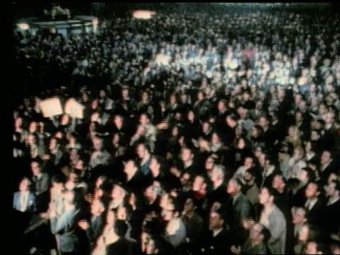 zoom in of vast crowd applauding at night