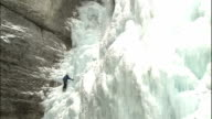 Zoom in on climber ascending craggy ice wall, Johnston Canyon, Canadian Rocky Mountains Park, Canada