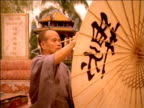 Zoom in on man painting Chinese characters on bamboo umbrella, China