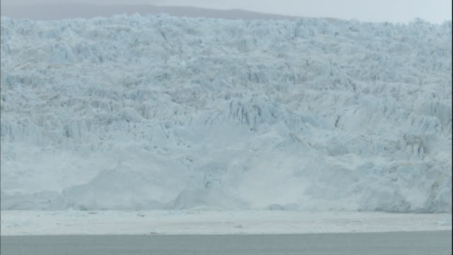 Zoom in on Sermeq Kujalleq glacier calving into Ilulissat Icefjord, Greenland