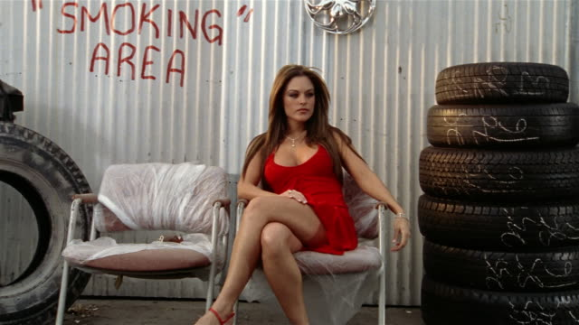 Zoom in on woman in red dress sitting on chair between tires with 'Smoking Area' spraypainted on corrugated metal wall behind her / looking at camera / Los Angeles, California