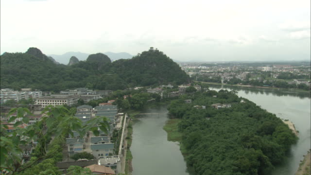 Zoom in over Li River to hill overlooking city