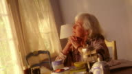 MS zoom in senior woman sitting at breakfast table drinking coffee thinking + looking somber