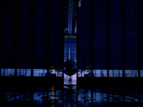 Zoom in through doors of hangar to wheel of aircraft