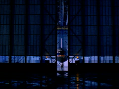 Zoom in through doors of hanger to wheel of aircraft parked inside