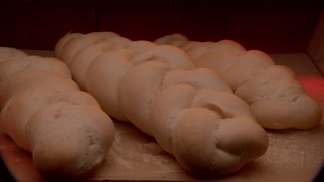 Zoom in time lapse three loaves of bread baking and turning brown in oven