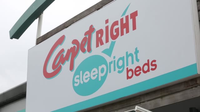 Zoom in to a logo for sleepright beds sits on a sign above the entrance to a Carpetright Plc carpet store in Basildon Pull out from sign above...