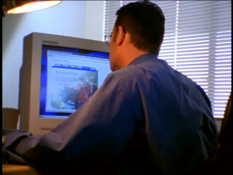 REAR VIEW zoom in to businessman working on computer looking at shopping related web site