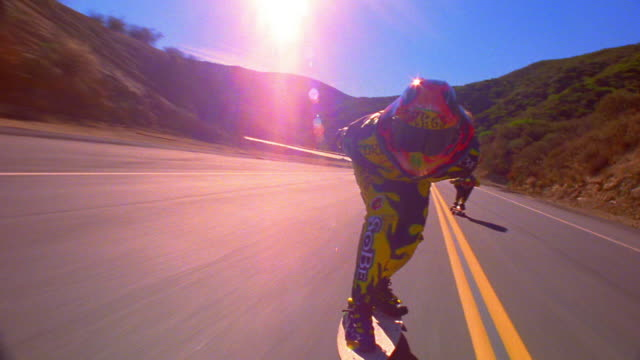 CANTED zoom in to close up two skateboarders with helmets speeding on mountain road / sun flare in shot