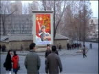 Zoom in to communist propaganda poster as citizens walk beneath North Korea 11 Mar 2003