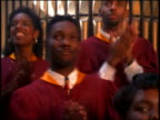 zoom in to extreme close up Black man in gospel choir singing + clapping in church