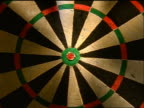 SLOW zoom in to extreme close up dart hitting bullseye on dart board