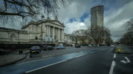 A zoom in towards the main entrance of the Tate Britain rapidly moving traffic passes along the embankment as people arrive at the gallery