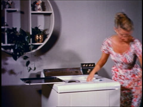 1950 zoom in woman loading clothing into + operating washing machine