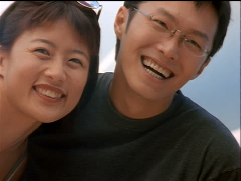 zoom in zoom out to close up Asian couple with arms around each other smiling + laughing outdoors