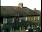 Zoom out and pan left across roof tops to wrecked houses and rubble from air crash Lockerbie Air Disaster 22 Dec 88