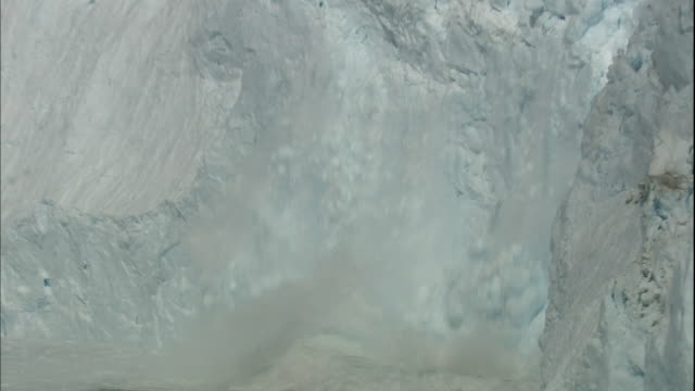 Zoom out as Sermeq Kujalleq glacier calves into Ilulissat Icefjord, Greenland