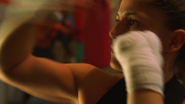 zoom out close up female boxer sparring w/heavy punching bag in gym, other female boxers working out in background